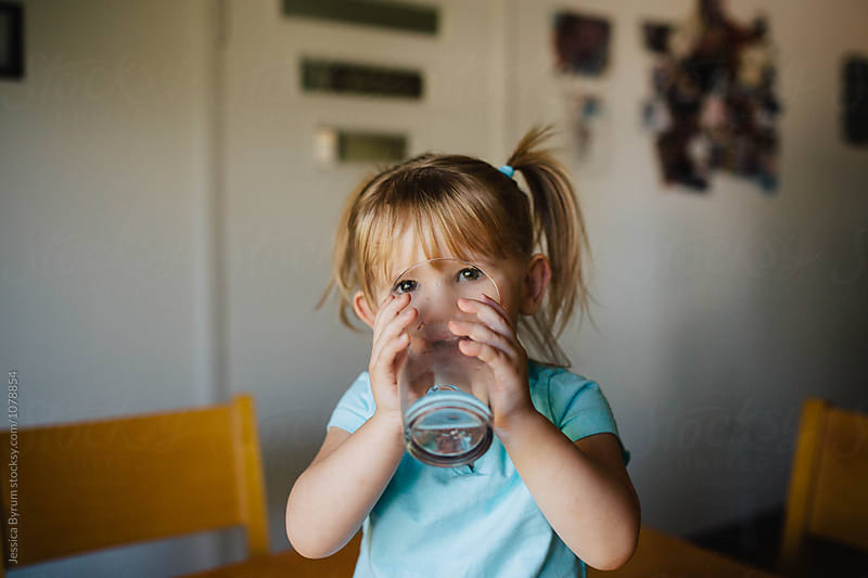 Toddler girl with pigtails sitting on the kitchen table drinking a big glass of water. by Jessica Byrum for Stocksy United