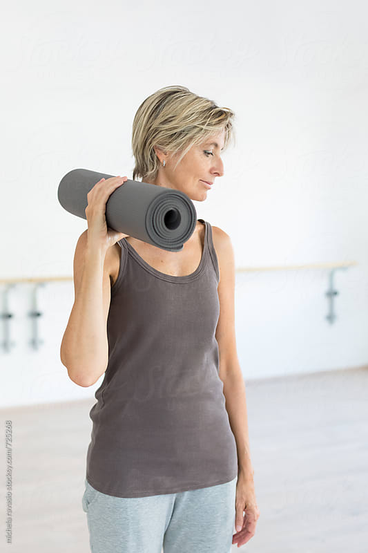 Mature woman holding the yoga mat by michela ravasio for Stocksy United