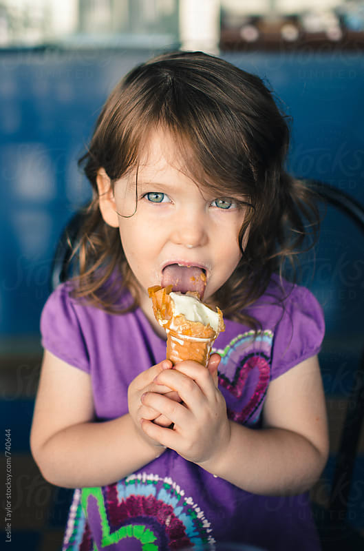 Young Girl Messily Eating Ice Cream by Leslie Taylor for Stocksy United