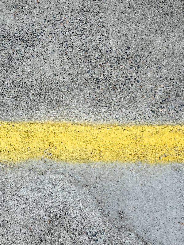 Painted yellow stripe on urban sidewalk and street by Paul Edmondson for Stocksy United