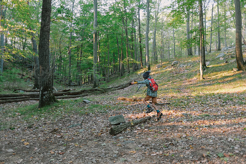 Young boy jumping over log in forest by kelli kim for Stocksy United