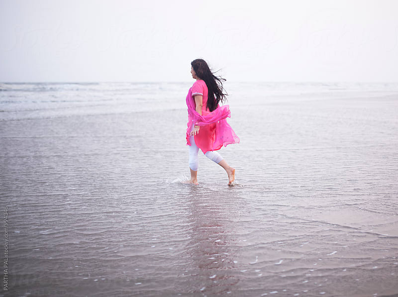 Indian woman walking alone in sea beach by PARTHA PAL for Stocksy United