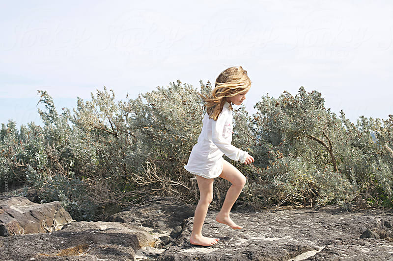 young girl running along rocks at the beach by Natalie JEFFCOTT for Stocksy United