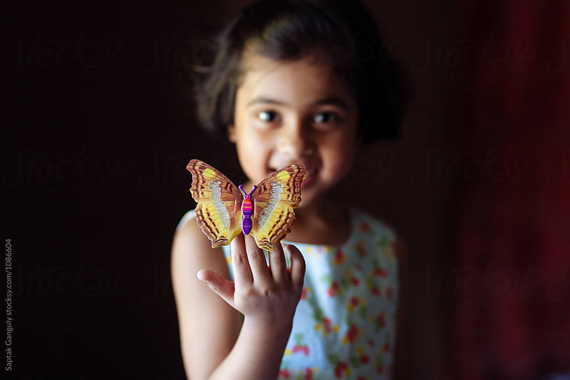 Little girl playing with decorative butterfly by Saptak Ganguly for Stocksy United