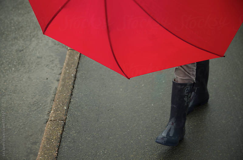 red umbrella held by someone on sidewalk by Léa Jones for Stocksy United