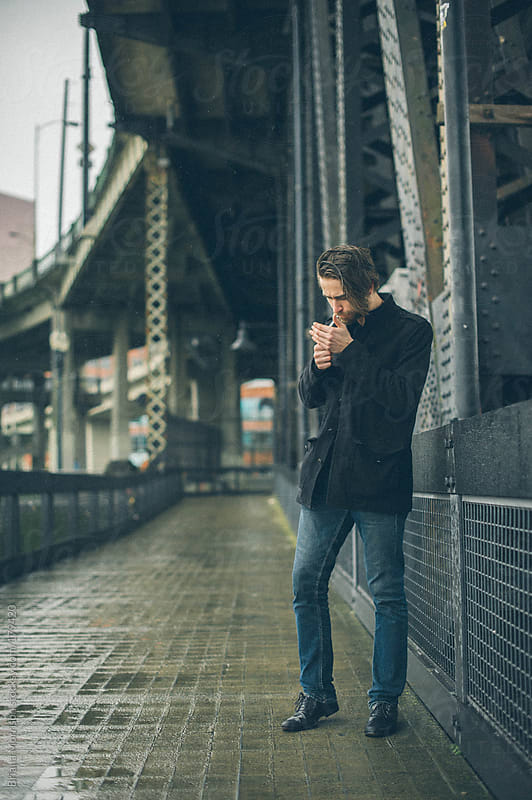 Man in Black Coat Lighting Cigarette on Industrial Metal Bridge by Briana Morrison for Stocksy United