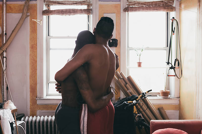 Black Gay Male Couple at Home Holding Each Other by Joselito Briones for Stocksy United