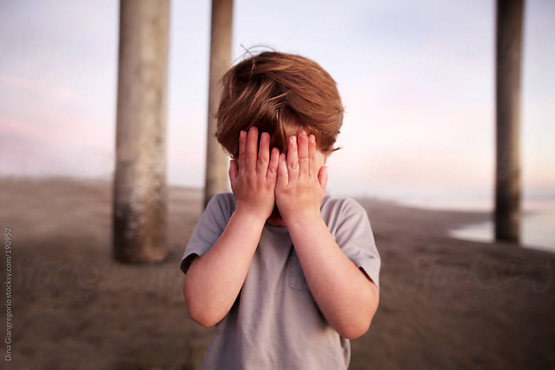 Little boy at beach covering his eyes by Dina Giangregorio for Stocksy United