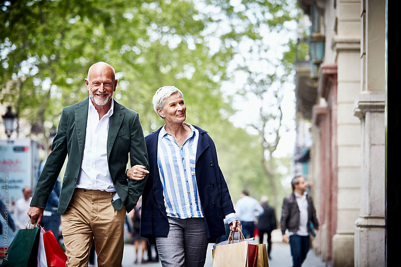 Senior Couple With Shopping Bags On Sidewalk by ALTO IMAGES for Stocksy United