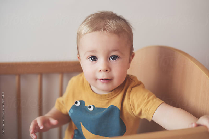 Portrait of a cute young boy standing in his cot and looking at camera by Lea Csontos for Stocksy United