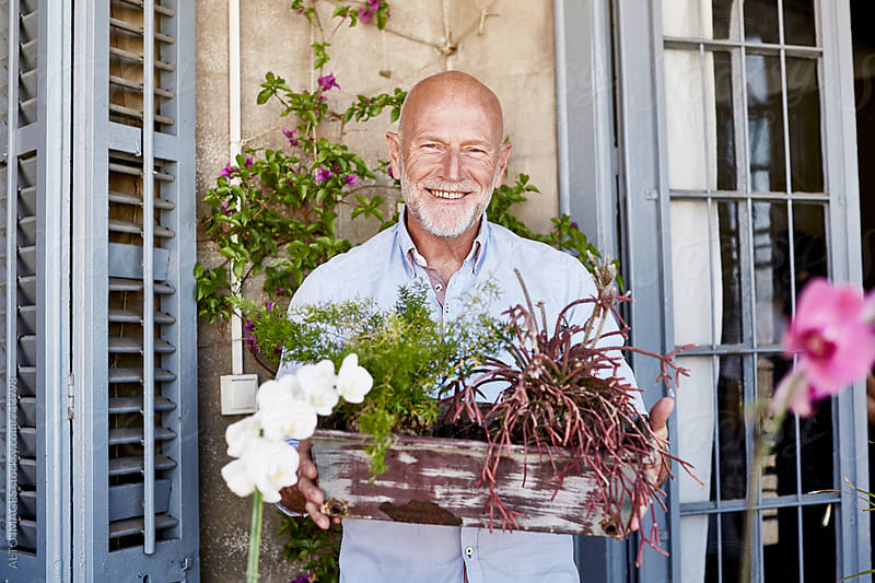 Senior Man Carrying Pot Plants On Balcony by ALTO IMAGES for Stocksy United