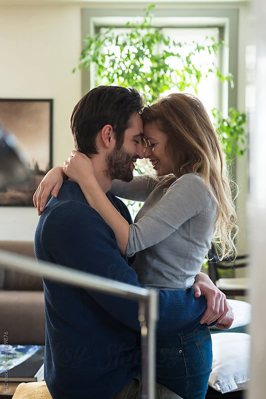 Happy young couple hugging at home by Simone Becchetti for Stocksy United
