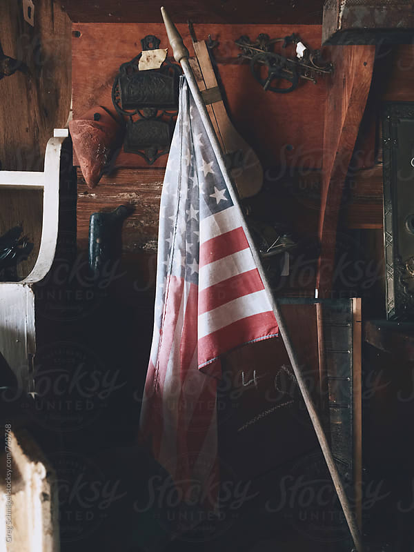 An old tattered American flag in a low lit room with natural light by Greg Schmigel for Stocksy United