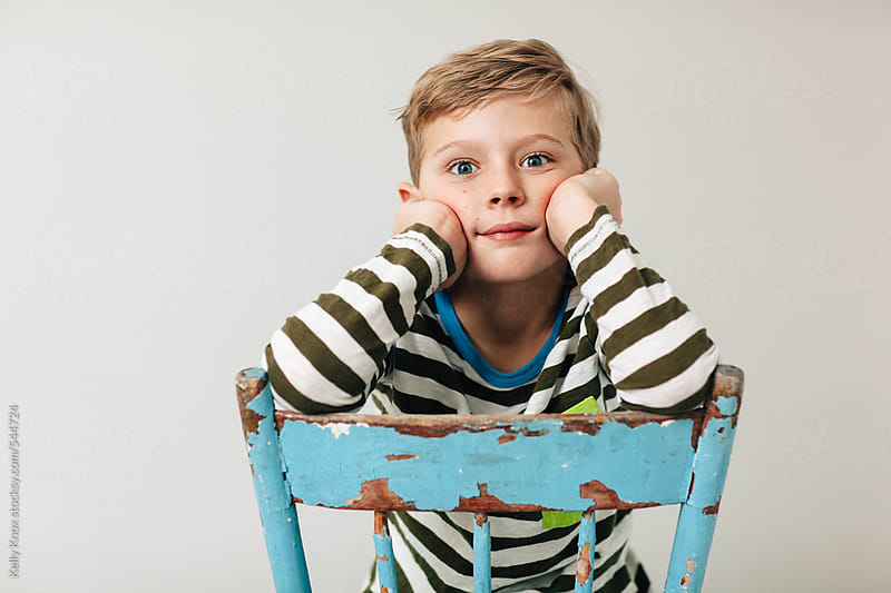 portrait of a boy exasperated with having his picture taken by Kelly Knox for Stocksy United