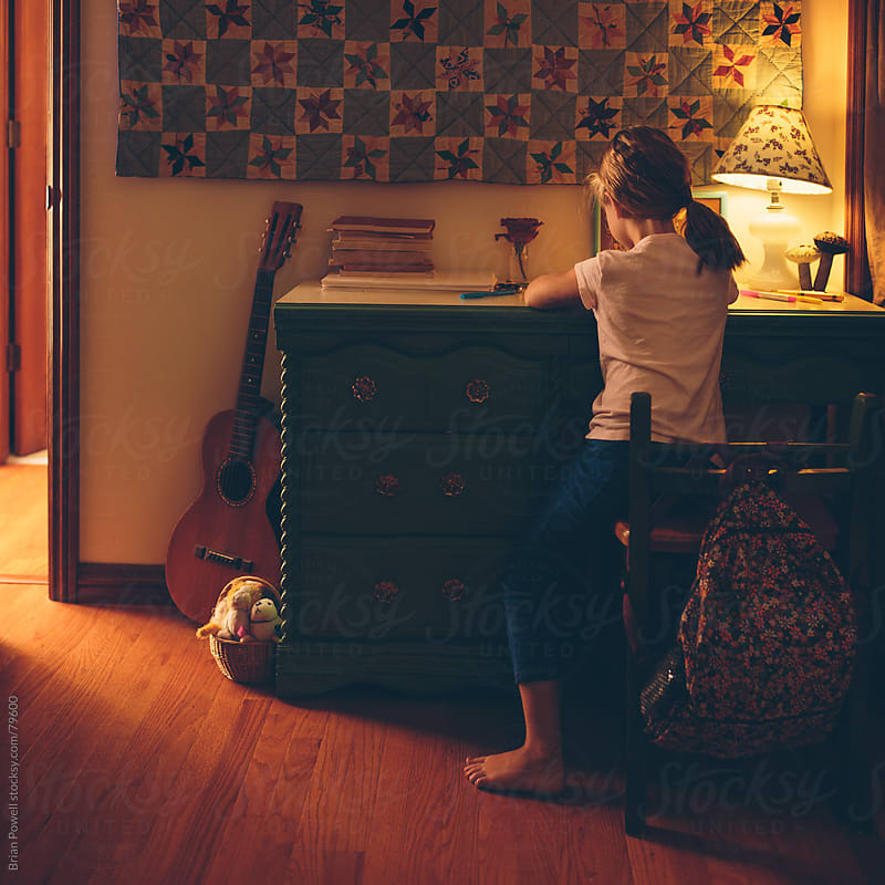 girl doing homework at night by Brian Powell for Stocksy United