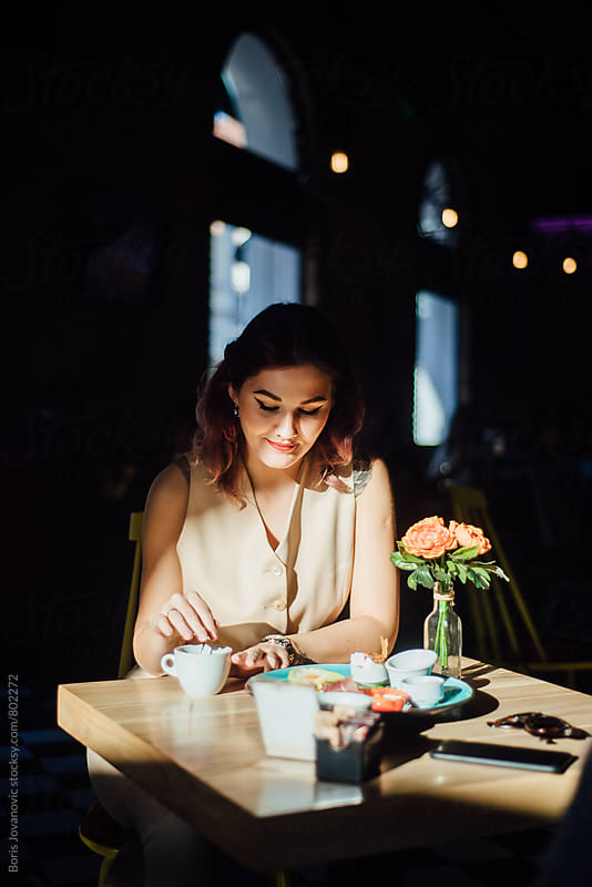 Woman having a breakfast in the cafe  by Boris Jovanovic for Stocksy United
