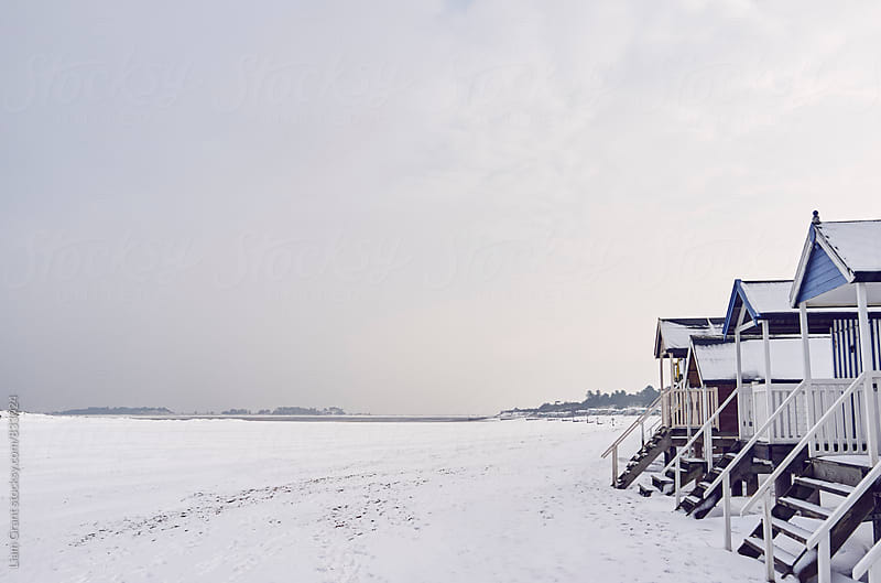 Beach huts covered in snow at low tide. Wells-next-the-sea, Norfolk, UK. by Liam Grant for Stocksy United