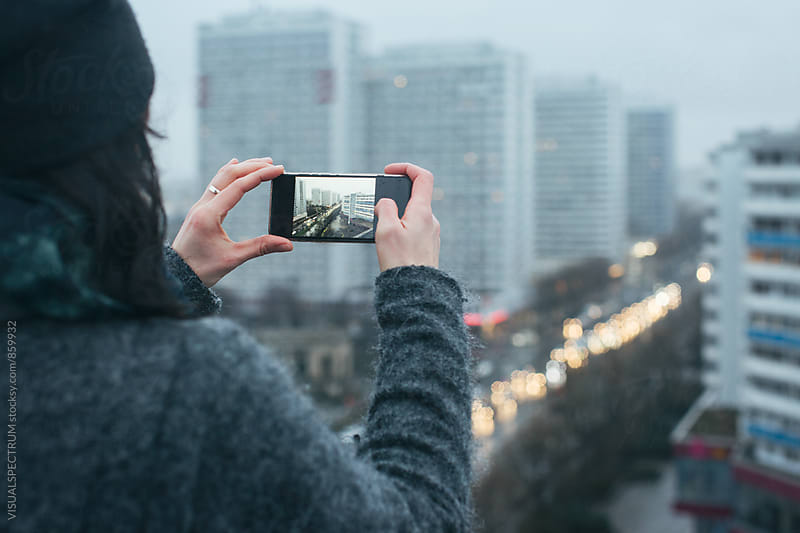 Woman Taking Photo with Smartphone on Berlin Rooftop on Rainy Winter Day by VISUALSPECTRUM for Stocksy United