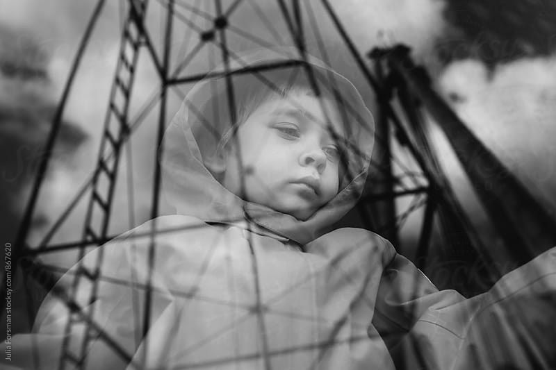 Child gazes sadly through a train window onto which mechanical structures are reflected. by Julia Forsman for Stocksy United