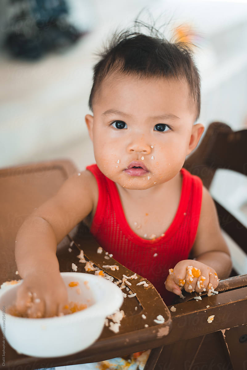 Asian baby eating rice. by Chalit Saphaphak - Stocksy United