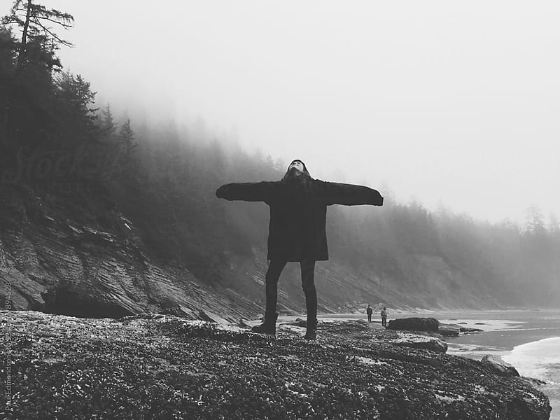 Twelve year old girl on beach with arms stretched  towards overcast sky by Paul Edmondson for Stocksy United