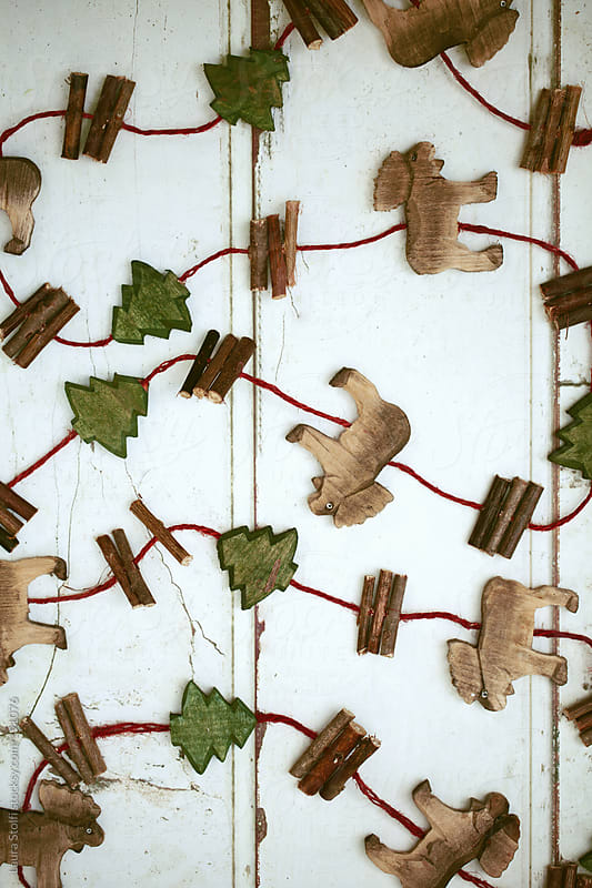 Pattern made with wooden carved reindeers and trees from ornamental handcrafted garland by Laura Stolfi for Stocksy United