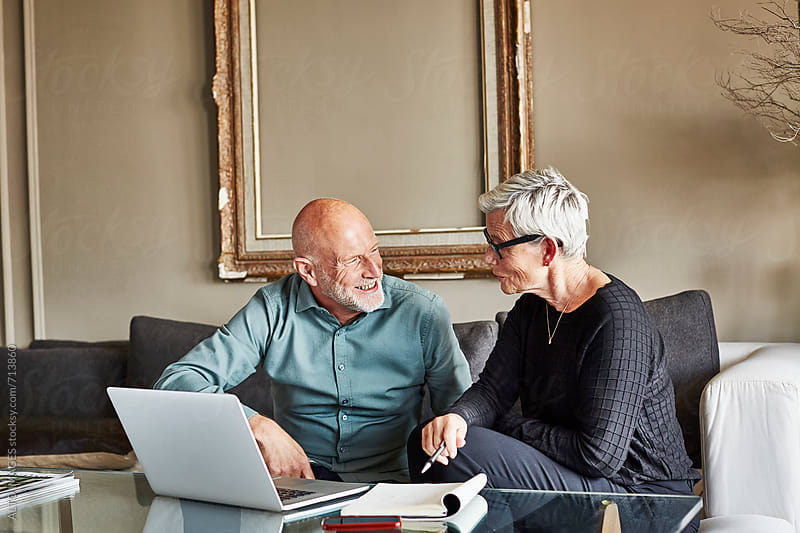 Senior Business Couple Discussing Over Laptop by ALTO IMAGES for Stocksy United