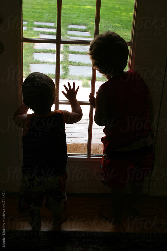 Two young children peer out of window, watching by Monica Murphy for Stocksy United