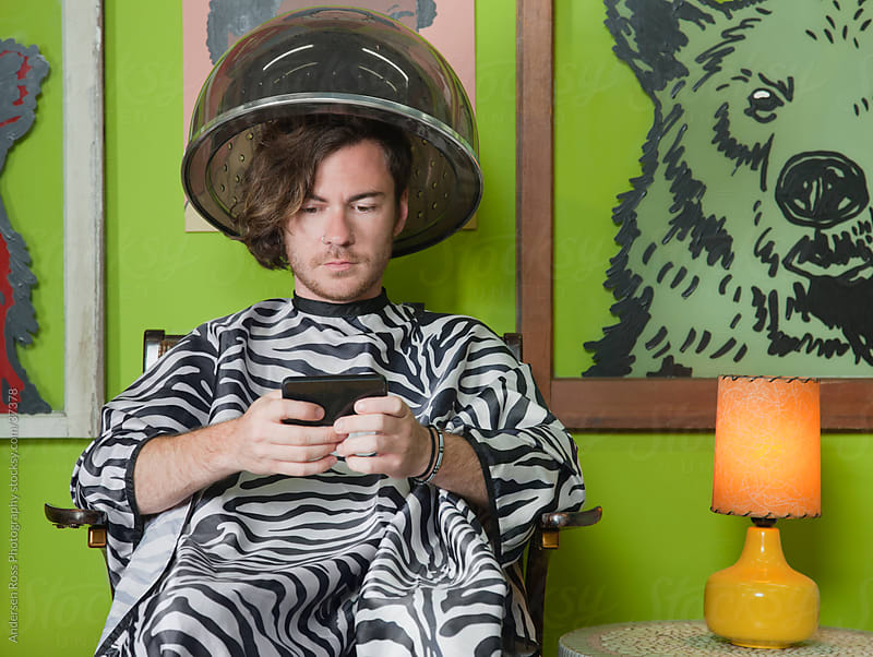 Young man sitting in hood hair dryer and texting by Andersen Ross Photography for Stocksy United