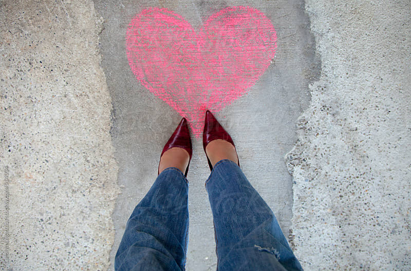 Woman in red heels and jeans standing over a pink chalk heart by Carolyn Lagattuta for Stocksy United