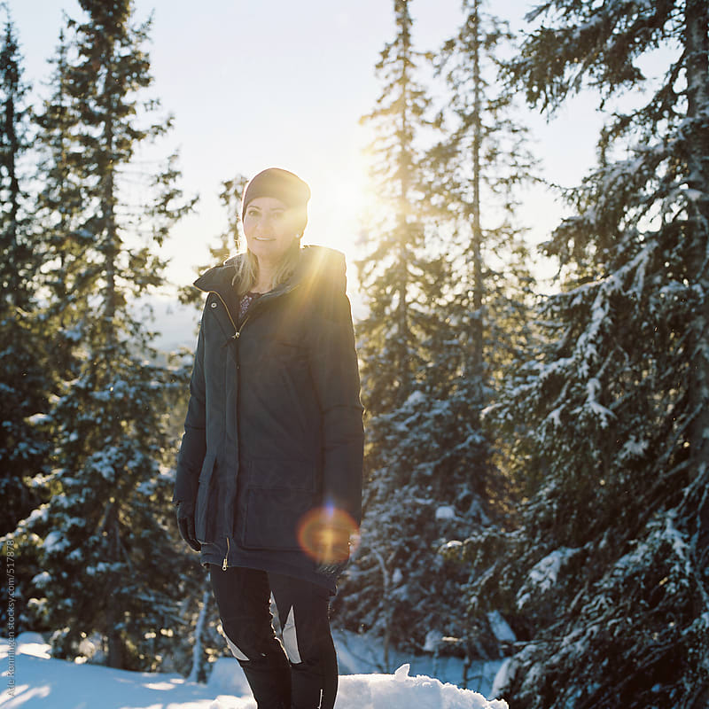 Young woman in outdoor jacket and purple hat enjoying the warm sun up in the mountains by Atle Rønningen for Stocksy United