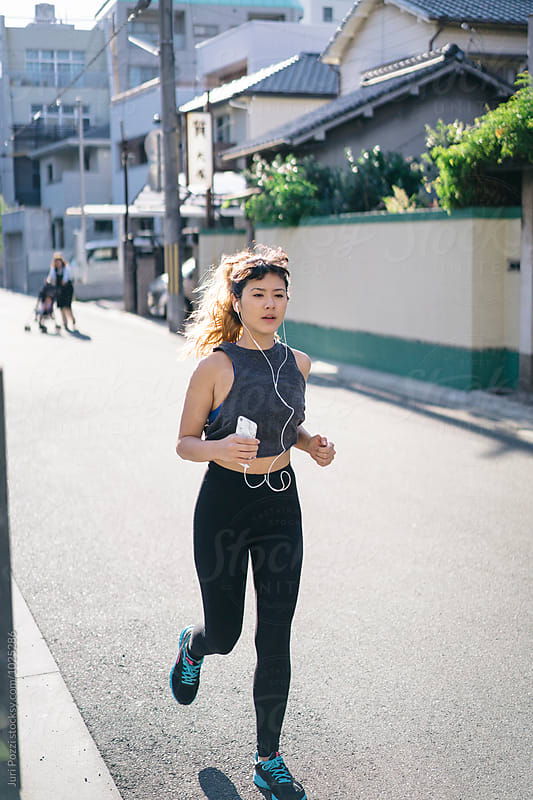 Fit Asian woman jogging in a city  by Juri Pozzi for Stocksy United