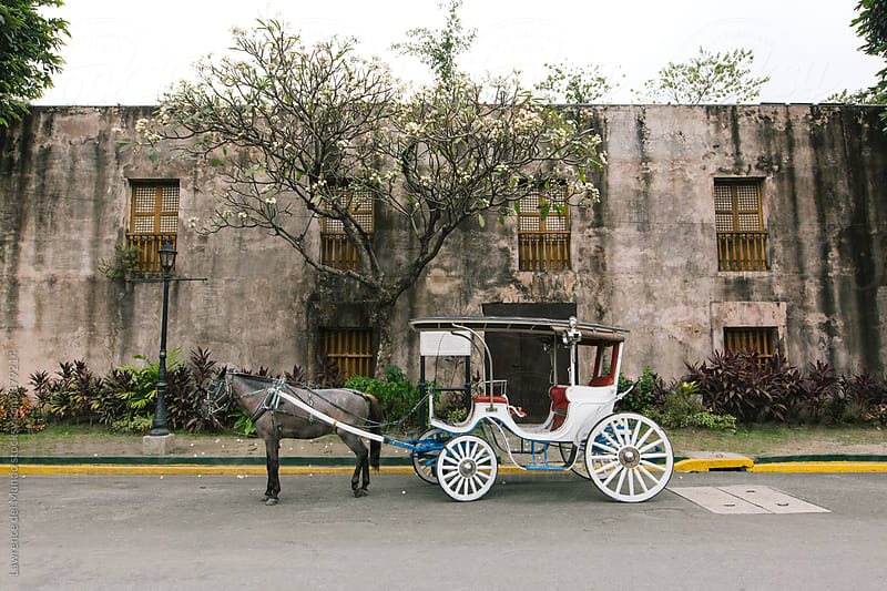 A white horse-drawn carriage parked in front of a Spanish colonial period wall with wooden windows by Lawrence del Mundo for Stocksy United