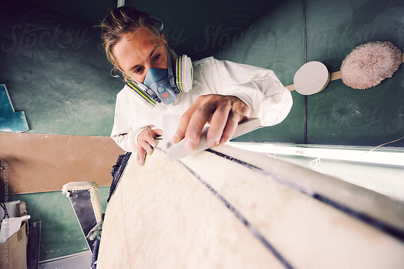 Shaper with gasmask sanding surfboard by Urs Siedentop & Co for Stocksy United