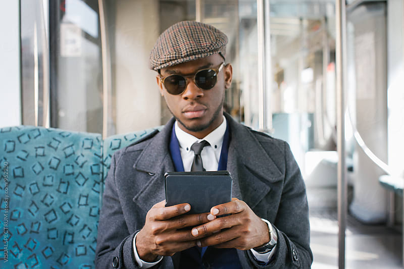 Portrait of Stylish Black Businessman Reading Ebook in Train by Julien L. Balmer for Stocksy United
