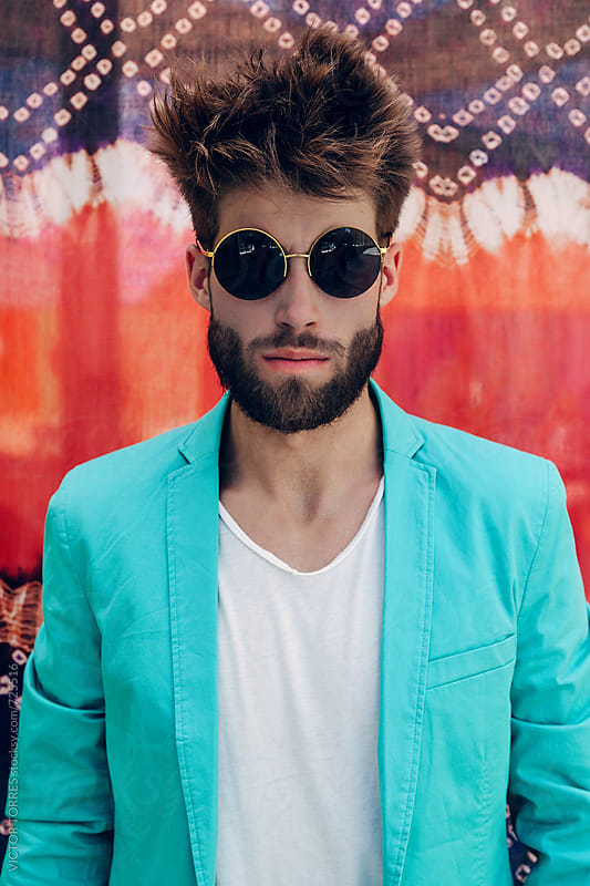 Stylish Man with Round Sunglasses Over a Colorful Background by VICTOR TORRES for Stocksy United