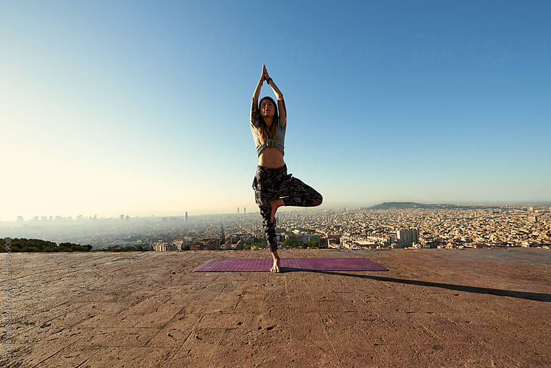 Woman in tree pose against of Barcelona cityscape by Guille Faingold for Stocksy United