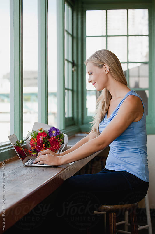 Woman using laptop at window by Andersen Ross Photography for Stocksy United