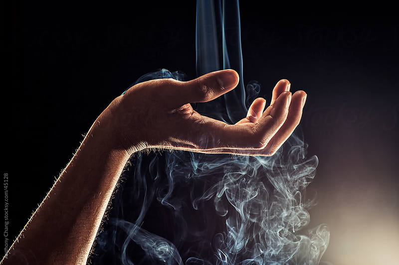 Smoke Falling Through Hand by Anthony Chang for Stocksy United