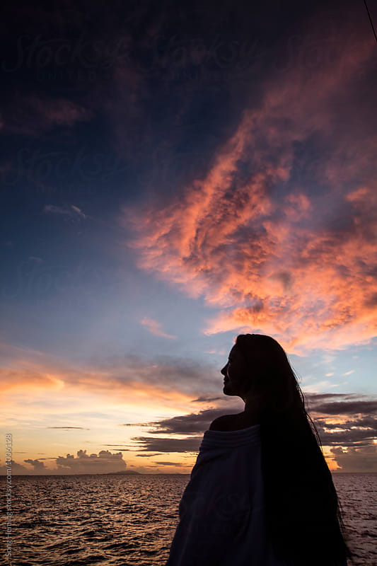 Girl looks at the sky at the seaside in sunset by Song Heming for Stocksy United