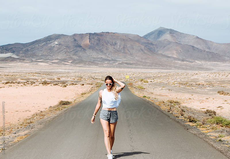 Woman walking down an endless road with mountains in the background by Susana Ramírez for Stocksy United