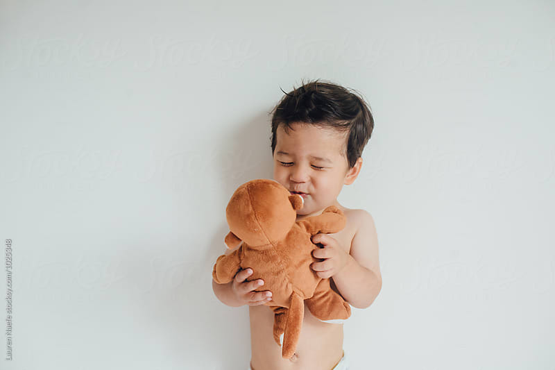 Child playing with stuffed animal by Lauren Naefe for Stocksy United