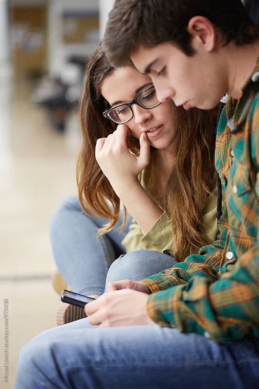 Young couple sharing and reading information with a phone by Miquel Llonch for Stocksy United
