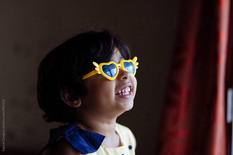 Little girl having fun wearing heart shaped sunglasses by Saptak Ganguly for Stocksy United