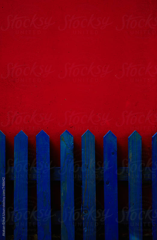 blue fence on red wall by Atakan-Erkut Uzun for Stocksy United
