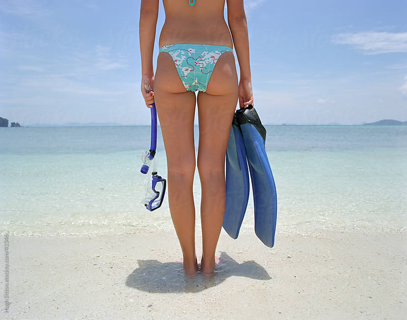 Woman in bikini at beach with mask and flippers. by Hugh Sitton for Stocksy United