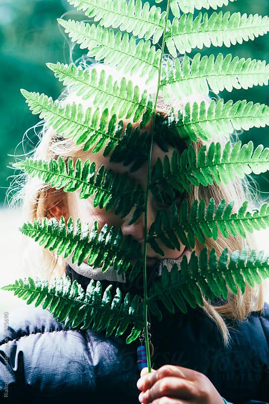 Cute five year old girl hiding behind large, green fern leaf by Paul Edmondson for Stocksy United