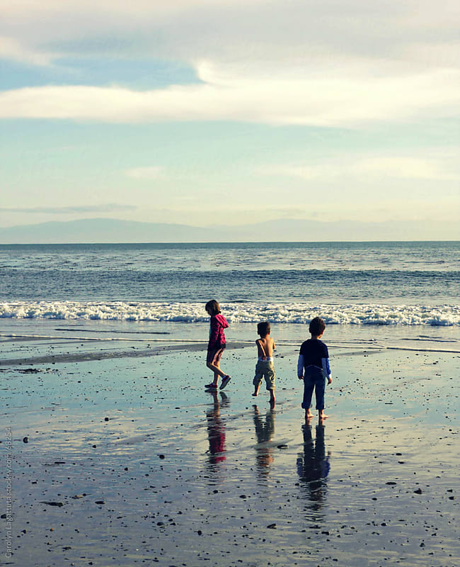Three children exploring on the beach by Carolyn Lagattuta for Stocksy United