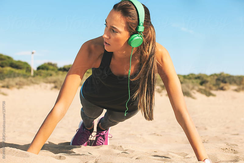 Fitness woman doing push ups on the beach. by BONNINSTUDIO for Stocksy United