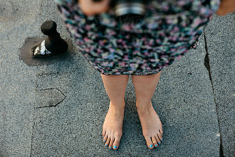 Feet of a young woman on a rooftop by VegterFoto for Stocksy United